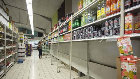 A woman walks in a supermarket where all packs of bottled water have been sold, in Pointe-a-Pitre, on the French overseas island of Guadeloupe on September 4, 2017, as part of preparations for arrival of Hurricane Irma. / AFP PHOTO / Helene Valenzuela (Photo credit should read HELENE VALENZUELA/AFP/Getty Images)