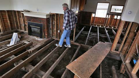 FILE - In this March 22, 2014 file photo, a man walks along the naked beams in the remains of his flood-damaged home in Lyons, Colo., destroyed in Sept. 2013. Houston's population is growing quickly, but when Harvey hit last weekend there were far fewer homes and other properties in the area with flood insurance than just five years ago, according to an Associated Press investigation. (AP Photo/Brennan Linsley, File)