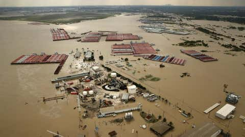 In this Aug. 30, 2017, photo, barges are secured by tugboats in the flood-swollen Burnet Bay along the Houston Ship Channel in Houston. (Tom Fox/The Dallas Morning News via AP)