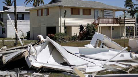 A member of a search and rescue team knocks on doors while checking on homes and their owners after Hurricane Irma in Goodland, Fla., Tuesday, Sept. 12, 2017. Canadian snowbirds who were lucky enough to escape property damage from hurricane Irma will still face higher costs as insurance providers jack up premiums and condo associations levy special assessments, say Florida insurance experts. THE CANADIAN PRESS/AP/David Goldman