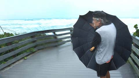 Patrick Danver, 67, of Satellite Beach, Fla. uses an umbrella to shield from the driving rain in South Patrick Shores, Fla., on Sept. 10, 2017 as Hurricane Irma made landfall in the state of Florida. (THE ASSOCIATED PRESS/Orlando Sentinel/Red Huber)