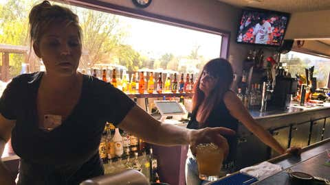 Crystal Maples, left, and Sally Kyle pour drinks at McCarty's Bar which turned into an evacuation center in Redwood Valley, Calif., Saturday, Oct. 14, 2017. Bartender Maples fled the wildfire after a harrowing escape to the bar Monday, and opened it to evacuees, many of which spent several days here. Mendocino County is 70 miles north of California's fabled wine country now under siege from wildfires but a world away in mood, attitude and, especially, prominence. (AP Photo/Paul Elias)