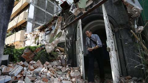 A man walks out of the door frame of a building that collapsed after an earthquake, in the Condesa neighborhood of Mexico City, Tuesday, Sept. 19, 2017. Throughout Mexico City, rescuer workers and residents dug through the rubble of collapsed buildings seeking survivors following a 7.1 magnitude quake. (AP Photo/Marco Ugarte)