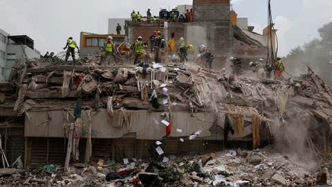 Workers shovel papers and debris off the top of the rubble of a building that collapsed in last week's 7.1 magnitude earthquake, at the corner of Gabriel Mancera and Escocia streets in the Del Valle neighbourhood of Mexico City, Monday, Sept. 25, 2017. Search teams were still digging through dangerous piles of rubble Monday, hoping against the odds to find survivors after the Sept. 19 quake.(AP Photo/Rebecca Blackwell)