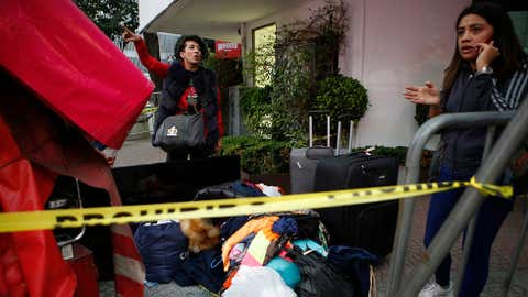 """A young woman stands on a street corner with her belongings after having to abandon her earthquake damaged apartment building, in the Roma neighborhood in Mexico City, Wednesday, Sept. 20, 2017. President Enrique Pena Nieto declared three days of national mourning even as authorities made rescuing the trapped and treating the wounded their priority. """"Every minute counts to save lives,"""" Pena Nieto tweeted. (AP Photo/Rebecca Blackwell)"""