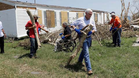Vice President Mike Pence, center right, and Texas Gov. Greg Abbott, center in wheel chair, help move debris during a visit to an area hit by Hurricane Harvey, Thursday, Aug. 31, 2017, in Rockport, Texas. (Eric Gay/AP)