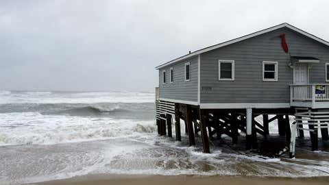 Waves wash ashore hitting a house as winds and storm surge from Tropical Storm Maria lash North Carolina's Outer Banks as the storm moves by well off-shore on Wednesday, Sept. 27, 2017. Dare County officials said the high tide flooded some roads in the area and travel is hazardous. (AP Photo/Ben Finley)