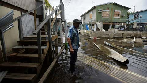 Juana Matos resident Hector Rosa walks through a flooded area after the passing of Hurricane Maria, in Puerto Rico, Wednesday, September 27, 2017. Since the devastating impact of said hurricane, the supply line of goods in general was interrupted in the US territory, causing endless rows in gas stations and commercial centres. (AP Photo/Carlos Giusti)