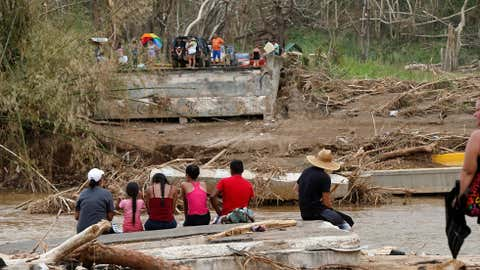 FILE - In this Wednesday, Sept. 27, 2017, file photo, people sit on both sides of a destroyed bridge that crossed over the San Lorenzo de Morovis River, in the aftermath of Hurricane Maria, in Morovis, Puerto Rico. Maria has thrown Puerto Rico's already messy economic recovery plans into disarray. (AP Photo/Gerald Herbert, File)