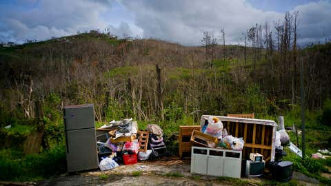 This Saturday, Oct. 14 2017 photo shows personal belongings recovered from a home destroyed by Hurricane Maria, in Morovis, Puerto Rico. Nearly a month after the hurricane made landfall, Puerto Rico is only beginning to come to grips with a massive environmental emergency that has no clear end in sight. With hundreds of thousands of people still without running water, and 20 of the island's 51 sewage treatment plants out of service, there are growing concerns about contamination and disease. (AP Photo/Ramon Espinosa)