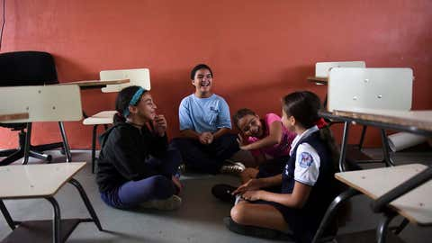 In this Friday, Oct. 13, 2017 photo, youths chat at the Ramon Marin Sola Elementary School, which opened its doors as a daytime community center after the passing of Hurricane Maria in Guaynabo, Puerto Rico. Children have been living in campus-turned-shelters in western Puerto Rico since Hurricane Maria flooded their homes, trying to pass the time while their families wait for help to replace the homes they lost in the storm. (AP Photo/Carlos Giusti)