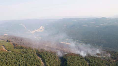 The Philpot Road wildfire is seen along a hillside just outside of Kelowna, B.C., on August 28, 2017. A municipal leader in British Columbia's central Interior says he wouldn't be surprised if wildfires that have chewed through more than 10,600 square kilometres of woodland won't be fully out until 2018. Chairman Al Richmond of the Cariboo Regional District said hot spots from many of the largest fires likely won't be doused until the spring, mirroring the Fort McMurray wildfire that Alberta officials said was finally declared extinguished on Aug. 2. THE CANADIAN PRESS/Jonathan Hayward [Close caption]