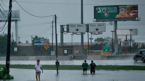 People walk dogs through flooded streets as the effects of Hurricane Harvey are seen August 27, 2017 in Galveston, Texas. ( BRENDAN SMIALOWSKI/AFP/Getty Images)