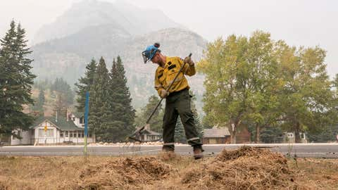 A fire crew member rakes up dead grass near the town of Waterton, Alta. in this undated handout photo. A popular national park in the southwestern corner of Alberta was under a mandatory evacuation order Friday because a forecasted shift in wind was expected to heighten the wildfire danger. Waterton Lakes National Park said the order covered the townsite and all other areas of the park except for Highways 5 and 6 and the Chief Mountain border crossing into the United States. (THE CANADIAN PRESS/Parks Canada, Nicholas Alexander)