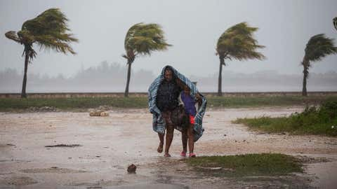 A woman and child use a blanket as protection from wind and rain as they walk in Caibarien, Cuba, Friday, Sept. 8, 2017. Hurricane Irma battered Cuba on Saturday with deafening winds and unremitting rain, pushing seawater inland and flooding homes before taking aim at Florida. (AP Photo/Desmond Boylan)