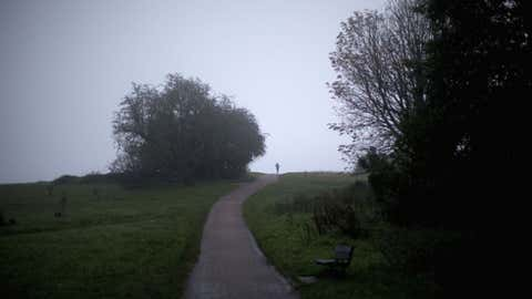 A woman jogs in misty conditions on Hampstead Heath in London on Oct. 20. (AP Photo/Matt Dunham)