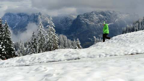 A stroller walks through the fresh snow at the Loferer Alp in the Austrian province of Salzburg, on Tuesday, Oct. 16. Snow fell down to just over 1,960 feet in several parts of the alpine country. (AP Photo/Kerstin Joensson)