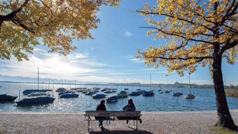 People take a rest on a bench at the shores of Lake Pfaeffikersee, near Pfaeffikon, Switzerland, on Oct. 19. Sunny and warm weather was predicted for the next few days. (AP Photo/Keystone/Walter Bieri)