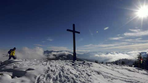 A hiker arrives the top of the Hochries mountain with a cross in front of the Alps near Rosenheim, southern Germany, Tuesday, on Oct. 16. (AP Photo/Matthias Schrader)