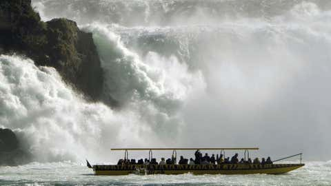 Tourists take a ride in a boat next to a waterfall of the river Rhine during sunny autumn weather in Neuhausen, Switzerland, on Oct. 20. (AP Photo/Keystone, Steffen Schmidt)