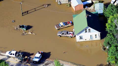 Victims of last week's devastating floods retrieve belongings outside a home near the East Platte River east of Greeley, Colo., Tuesday, Sept. 17, 2013. The area's broad agricultural flatlands were especially hard hit by the high water. (AP Photo/John Wark)