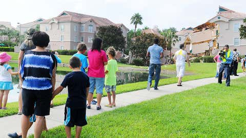 People stand near a partially collapsed building over a sinkhole at Summer Bay Resort near Disney World on Aug. 12, 2013 in Clermont, Florida. (Gerardo Mora/Getty Images)
