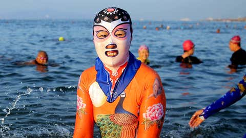 Women and men wearing siamesed facekinis play in water on August 29, 2016 in Qingdao, Shandong Province of China. Facekini has been China's popular beach trend and the latest siamesed facekini designed with various patterns like dragon, phoenix and peacock and many others catered to women and men's pleasure. Different from the old facekini protecting head only, the siamesed facekini kept your head and upper body away from sunshine. (Photo by VCG via Getty Images)
