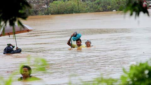 Residents of Fiji's Korociri settlement cross through a flooded backroad on April 4, 2016. (Fijian Government/Facebook)