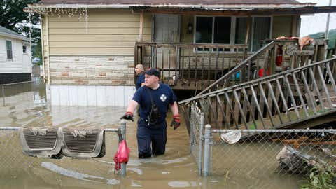 Bridgeport, West Virginia, fireman Ryan Moran exits a home as he and a crew search homes in Rainelle, W.Va., Saturday, June 25, 2016. Heavy rains that pummeled West Virginia left multiple people dead, and authorities said Saturday that an unknown number of people in the hardest-hit county remained unaccounted for. (AP Photo/Steve Helber)