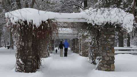 Max and Shaina Richardson walk their dog through the snow. (AP Photo/Rick Bowmer)