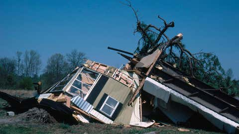 A trailer, demolished by a tornado, is twisted around an uprooted tree. North Carolina,