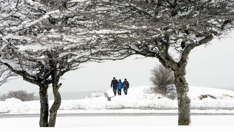 People walk along the coast line at Kettle Cove in Cape Elizabeth during Monday's snowfall, March 21, 2016. The family is visiting Maine for a Spring Vacation. (Shawn Patrick Ouellette/Portland Press Herald via Getty Images)