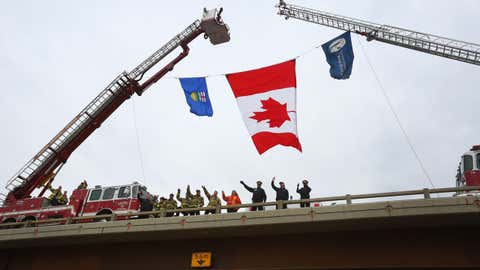 Firefighters and Royal Canadian Mounted Police (RCMP) officers greet returning residents from an overpass on Highway 63 just outside Fort McMurray, Alberta, on June 1, 2016. Tens of thousands of Fort McMurray residents were expected to begin trickling back into the Canadian oil city ravaged by wildfires almost a month after the blaze was declared no longer a threat.
