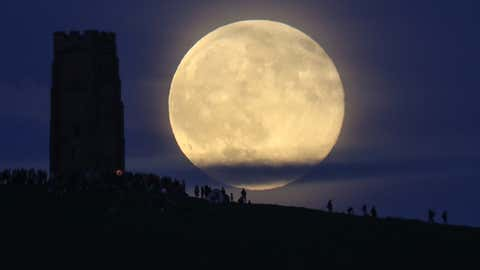 A full moon rises behind Glastonbury Tor as people gather to celebrate the summer solstice on June 20, 2016 in Somerset, England. Last night's strawberry moon, a name given to the full moon in June by Native Americans because it marks the beginning of strawberry picking season, last occurred on the solstice on June 22, 1967 and it will not happen again on the summer solstice for another 46 years until June 21, 2062.  (Matt Cardy/Getty Images)