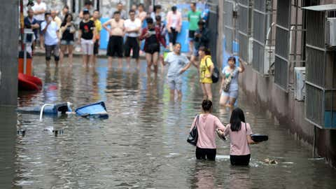 This photo taken on July 21, 2016, shows people making their way through a flooded area in Changping District in Beijing, China.