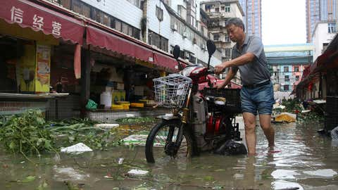 A man pushes a motorbike through a flooded street in Xiamen, in China's eastern Fujian province after Typhoon Meranti made landfall on September 15, 2016. Typhoon Meranti made landfall in Fujian early on September 15, with winds up to 230kph, knocking out electricity in some areas and causing rail delays. (STR/AFP/Getty Images)