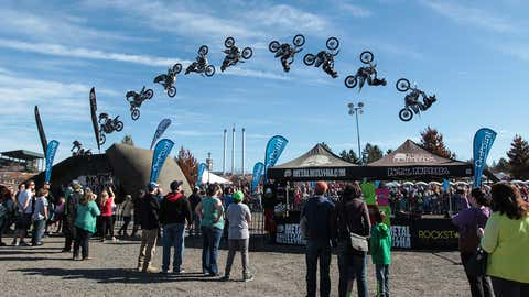 Bend, OR, USA - January 14, 2016: A professional motorcycle rider for the Metal Mulisha performs a backflip for a crowd of people celebrating at the WinterFest event.  As the Winters lengthen, Winterfest has been adding more warm weather sports to the event.