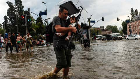 A pedestrian carries a child in a stroller as he crosses a flooded street in Besiktas near Istanbul, Turkey, on July 27, 2017. (BULENT KILIC/AFP/Getty Images)