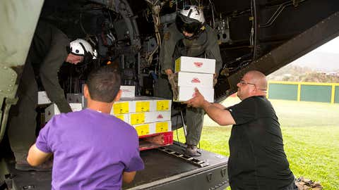 In this U.S. Navy handout, Marines assigned to Marine Medium Tiltrotor Squadron (VMM) 162, embarked aboard the amphibious assault ship USS Kearsarge (LHD 3), and local volunteers unload food from an MV-22 Osprey September 27, 2017 in Jayuya, Puerto Rico. Kearsarge is assisting with relief efforts in the aftermath of Hurricane Maria. The Department of Defense is supporting the Federal Emergency Management Agency, the lead federal agency, in helping those affected by Hurricane Maria to minimize suffering and is one component of the overall whole-of-government response effort. (Ryre Arciaga/U.S. Navy via Getty Images)