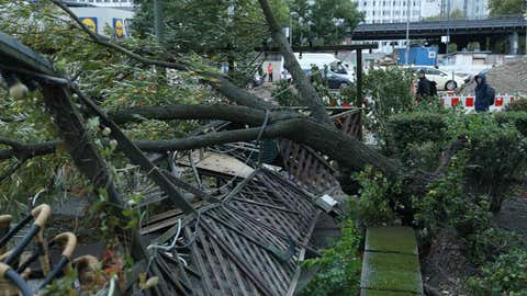 People walk past a tree that was uprooted and smashed a restaurant's outdoor patio during a storm front on Oct. 5, 2017, in Berlin, Germany. Storm front 'Xavier' is hitting northern and central Germany hard, leading to the closure of airports, rail lines, commuter trains and buses and even highways across the region. (Sean Gallup/Getty Images)
