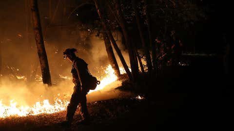 CalFire firefighter Brandon Tolp uses a drip torch during a firing operation while battling the Tubbs Fire on October 12, 2017 near Calistoga, California. At least thirty one people have died in wildfires that have burned tens of thousands of acres and destroyed over 3,500 homes and businesses in several Northern California counties.  (Justin Sullivan/Getty Images)