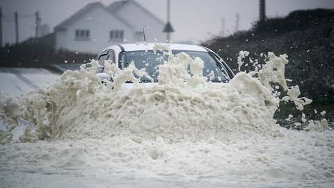 A car drives through sea foam whipped up by the wind of Hurricane Ophelia at Trearddur Bay on October 16, 2017 in Holyhead, Wales. Hurricane Ophelia comes exactly 30 years after the Great Storm of 1987. Two people have been killed as the remnants of the storm hit the United Kingdom and Ireland.  (Christopher Furlong/Getty Images)