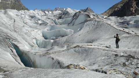 A hiker standing on the Aletsch glacier photographs an ice landscape on August 23, 2016 near Bettmeralp, Switzerland. (Sean Gallup/Getty Images)
