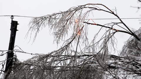 Power lines on spark after a tree fell onto the wire due to heavy ice during Monday's ice storm, Monday, Dec. 28, 2015 in Burlington, Iowa.  (Lauren Kastner/The Hawk Eye via AP)
