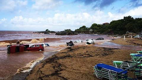 Abandoned cars are piled into the sea after being washed away by torrential rainfall and flooding in Greece on Sept. 7, 2016.