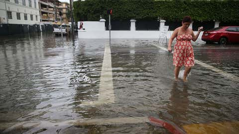 Zsuzsa Nagy walks through a flooded street that was caused by the combination of the lunar orbit which caused seasonal high tides and what many believe is the rising sea levels due to climate change on September 29, 2015 in Miami Beach, Florida. The City of Miami Beach is in the middle of a five-year, $400 million storm water pump program and other projects that city officials hope will keep the ocean waters from inundating the city as the oceans rise even more in the future.  (Joe Raedle/Getty Images)