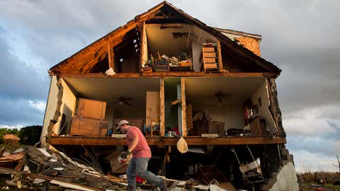 Nick Mobley helps clean up a house owned by a family friend, Wednesday, Feb. 24, 2016, after a storm hit Appomattox County, Va. A powerful storm system swept across the East Coast on Wednesday, knocking out power to tens of thousands of homes and businesses in the region. (Jill Nance/The News & Advance via AP)