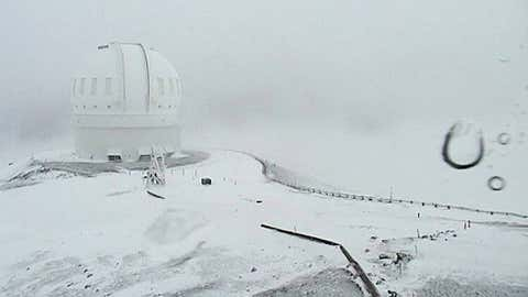 In this image made from webcam video provided by Canada-France-Hawaii Telescope, the CFHT telescope on the summit of Mauna Kea on Hawaii's Big Island is covered in snow on Thursday, Dec. 1, 2016. (Canada-France-Hawaii Telescope via AP)