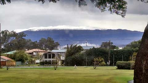 This photo provided by Grant Matsushige, an Instrumentation Specialist at the Canada-France-Hawaii Telescope, shows the summit of Mauna Kea on Hawaii's Big Island covered in snow as seen from Waimea, Hawaii on Thursday, Dec. 1, 2016. (Grant Matsushige/Canada-France-Hawaii Telescope via AP)