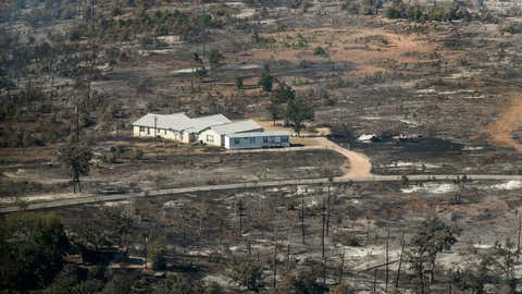 In this aerial photo, a home surrounded by burned landscape appearsspared from the Hidden Pines Fire near Smithville, Texas, Friday, Oct. 16, 2015. A preliminary investigation indicates a farming accident sparked the wildfire that's consumed more than 7 square miles and destroyed 40 structures in Central Texas, authorities said Friday. (Rodolfo Gonzalez/Austin American-Statesman via AP)